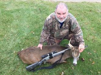 Man kneeling in grass showing the deer he shot during deer hunting season.