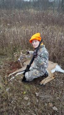 Boy with his gun and deer he shot during hunting season.