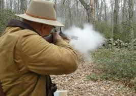 Man shooting a black powder rifle in the woods.